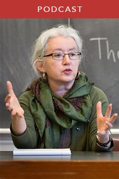 Professor Janet Gyatso talking and gesturing from behind a desk while teaching class